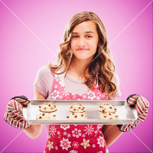 Caucasian teenager holding tray of fresh cookies