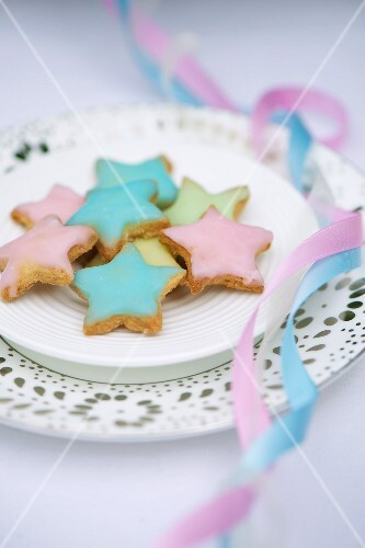 Star-shaped biscuits decorated with pastel-coloured icing sugar for a baptism party
