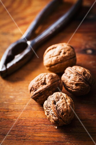 Walnuts and a nutcracker on a wooden surface