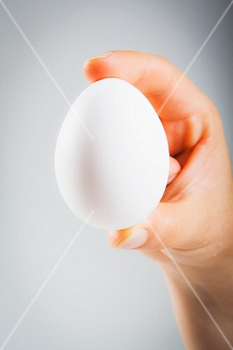 A woman's hand holding a white egg