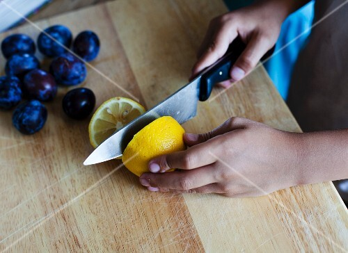 A girl cutting a lemon in half with a knife