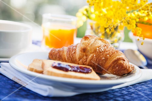 A breakfast of croissant, rusk and fresh orange juice