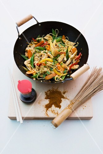 Strips of turkey stir-fried in a wok with vegetables and noodles