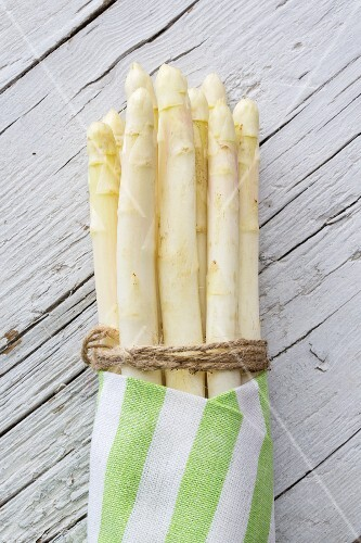 White asparagus, tied in a bundle, in a striped cloth