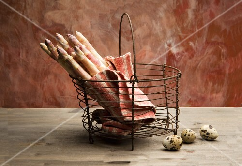 White asparagus in a wire basket with quail's eggs