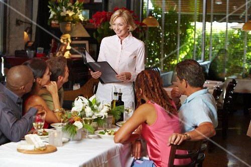 A waitress presenting the menu to diners in a restaurant