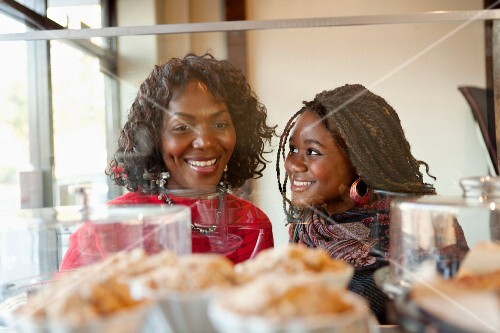 A dark-skinned mother and her adult daughter in front of a display in a cafe