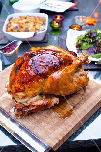 A roast turkey on wooden board