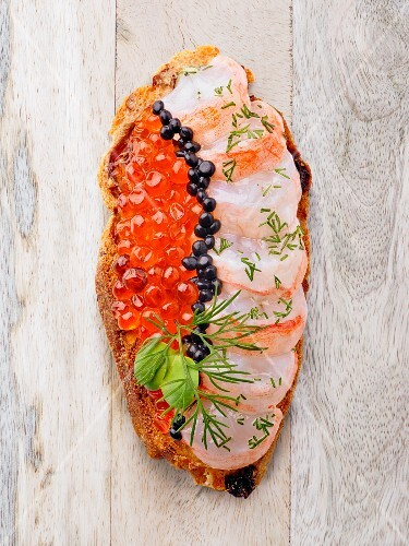 A slice of bread topped with fish and caviar