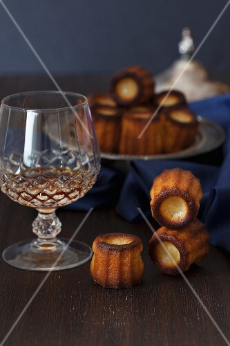 Canelés de Bordeaux (sweet French cakes) and liqueur in a crystal glass