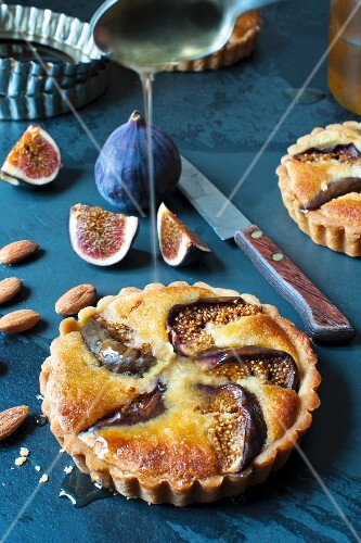 An individual fig and almond tart with honey, fresh figs and a knife.