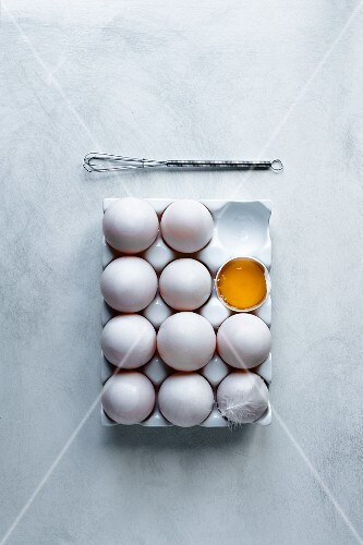 Eggs, one open in a white tray with a feather and a whisk.