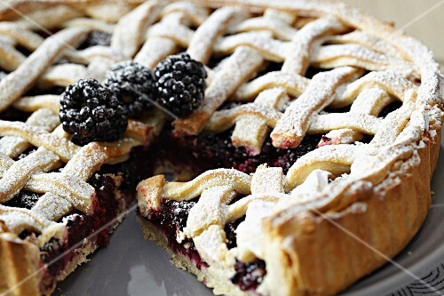 A sliced blackberry tart with a lattice pastry top