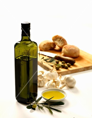 Bottle of olive oil with garlic olives and bread