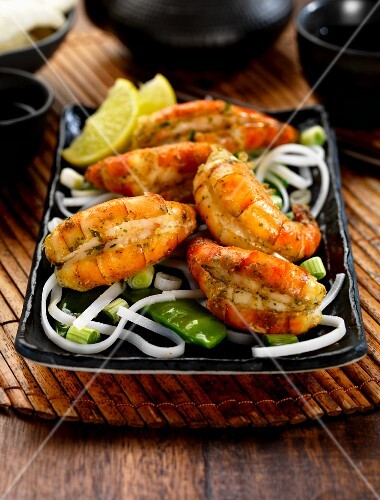 garlic and herb king prawns with rice noodles spring onions and sugar snap peas