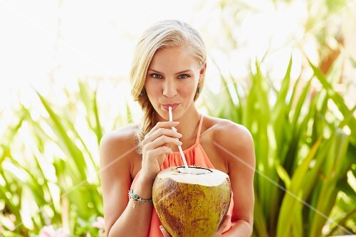 Caucasian woman drinking from coconut