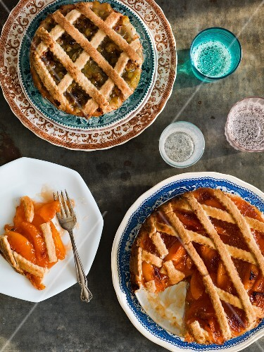 Gooseberry and peach pies with lattuce crust on vintage plates with colored glasses on an antiqued metal surface