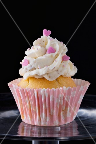 A cupcake decorated with buttercream and pink hearts