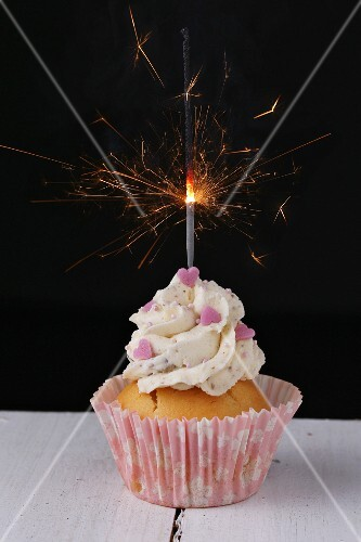 A cupcake decorated with pink hearts and a sparkler