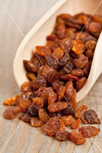 Sultanas on a wooden scoop (close-up)