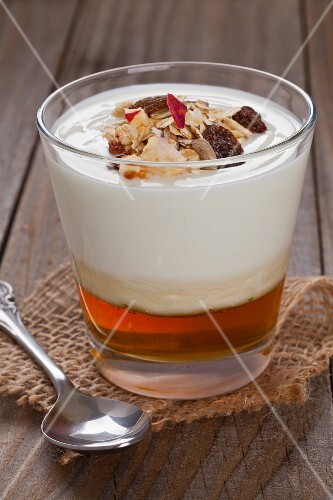 Natural yogurt on honey topped with fruit muesli in a glass