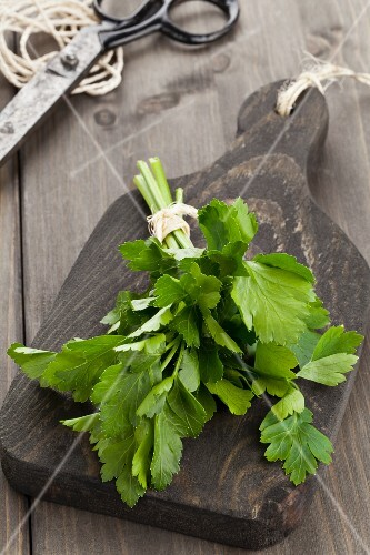 A bunch of smooth parsley on a wooden board