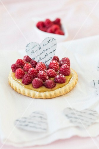 A raspberry tartlet decorated with a paper heart