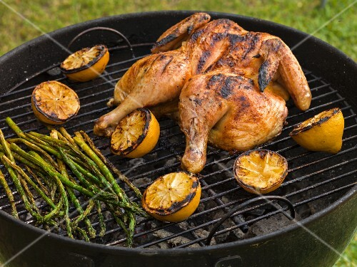 Whole chicken, split on the grill surrounded by lemons with asparagus