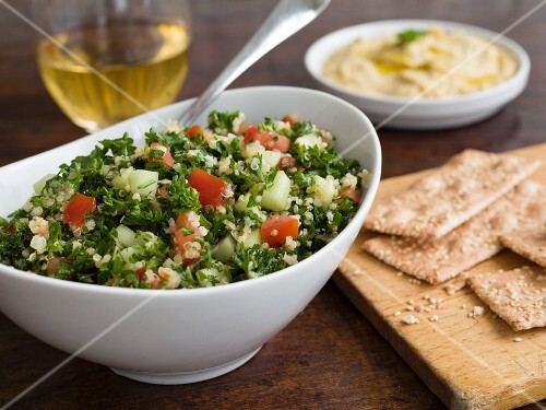 Tabbouleh with parsley, cucumber and tomato and crackers and hummus