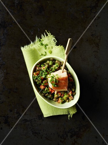 Lentils with a salmon skewer in a bowl