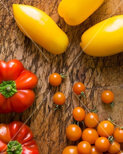 Yellow roma tomatoes, orange cherry tomatoes and heirloom peppers on an old chopping board