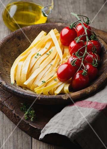 Tagliatelle and cherry tomatoes in a wooden bowl