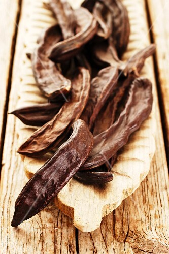 Carob bean pods in a wooden dish