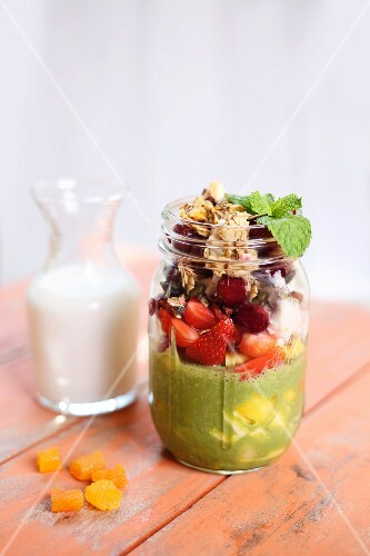 Breakfast parfait with pumpkin seed milk, berries and dried apricots