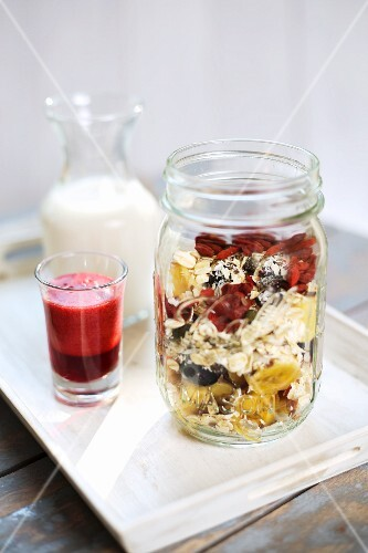 Breakfast parfait with goji berries, bananas, cashew nuts, milk and raspberry sauce