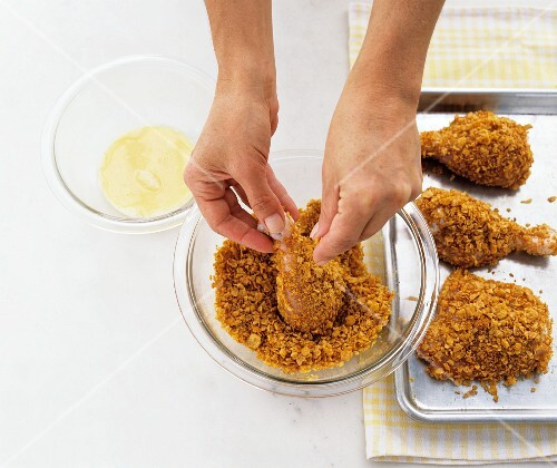 Chicken legs being coated with cornflakes