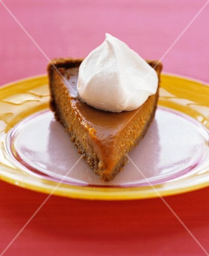 A slice of sweet potato pie with a dollop of cream