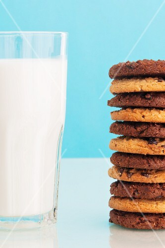 A glass of milk next to a stack of cookies