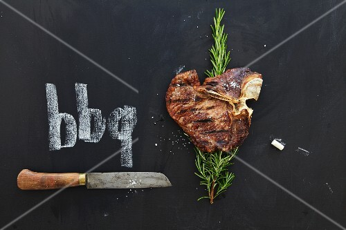 A grilled T-bone steak with rosemary and knife on a chalkboard