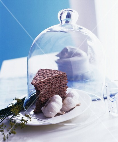 Crisp breads and garlic under a decorative glass cloche
