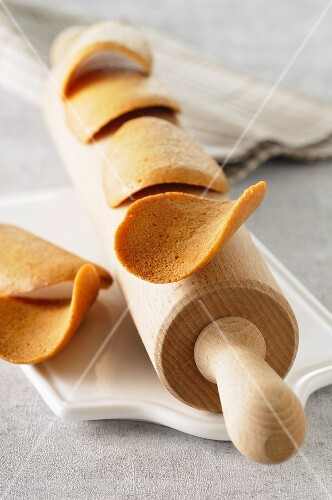 Tuiles (wafer biscuits, France) on a rolling pin