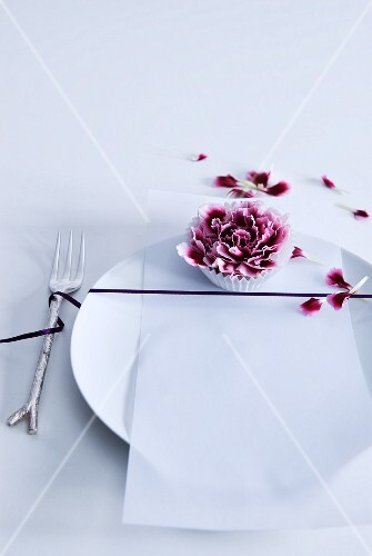 Place setting decorated with black ribbon and purple carnation bloom in paper cake case