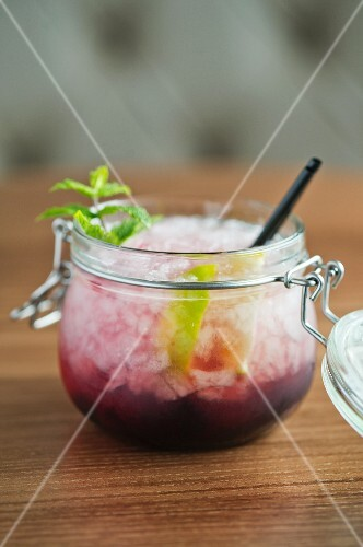 A blackberry cocktail with rum and ice cubes