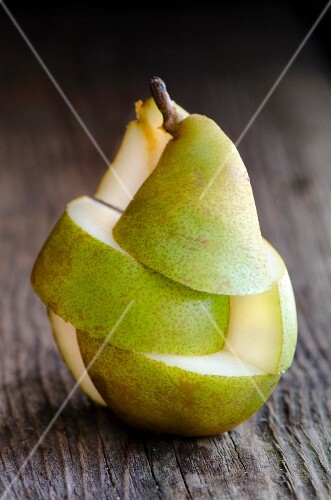 A whole pear, cut into segments, on a wooden surface