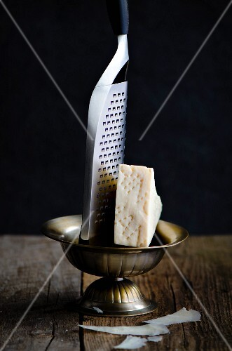 A slice of Pecorino Romano cheese with a greater in a metal bowl