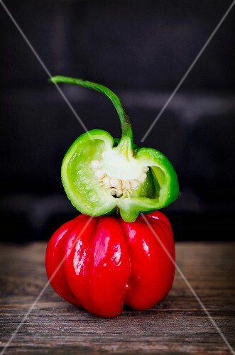 Red and green Scotch Bonnet chilli peppers, whole and halved