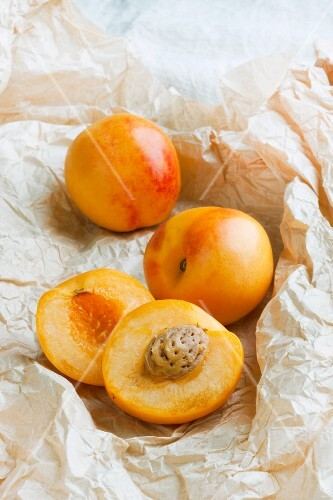 Whole and halved nectacots (a cross between a nectarine and an apricot)