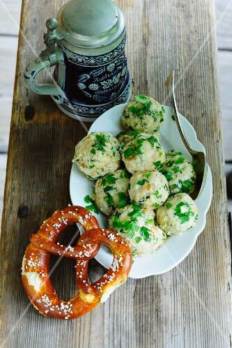 Bread dumplings with parsley next to a pretzel and an old-fashioned tankard