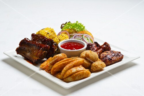 Spare ribs and chicken wings with potato wedges, corn on the cob and ketchup
