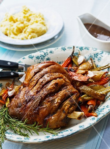 Roast shoulder of lamb with vegetables, rosemary, mashed potatoes and gravy